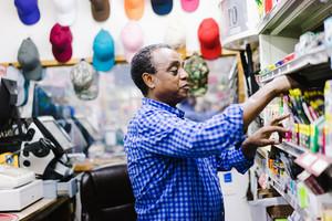older black man getting something off store shelf