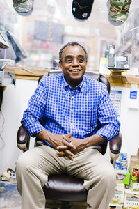 older black man sitting in chair and smiling