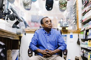 older black man sitting in chair behind store counter