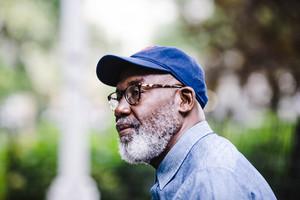 Older black man wearing blue cap