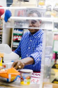 older black man working as cashier