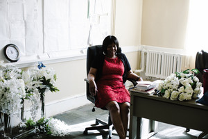 Older Black woman sitting surrounded by flowers
