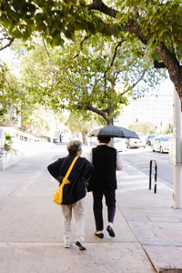 older couple walking down street with umbrella