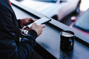 person charges phone while drinking coffee on a bar