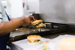 Person cooking a hamburger