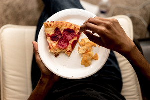 person eats a slice of pizza