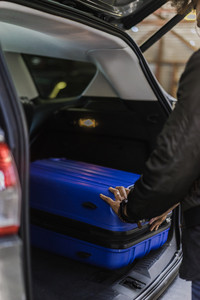 Person packing suitcase in car