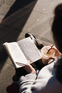 person writing in book sitting outside with iced coffee drink