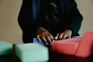 schoolgirl plays with building blocks