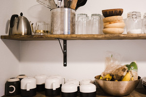 Shelf of kitchen bowls, plates and appliances