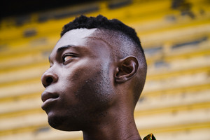 side profile of black man's face in front of yellow wall