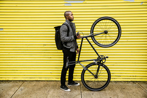 side view black man holding bicycle up on back tire yellow garage