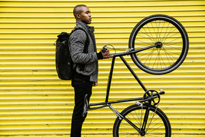side view black man standing straight holding bicycle on back tire yellow garage