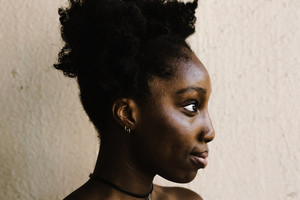 side view of a Black woman standing up against a wall