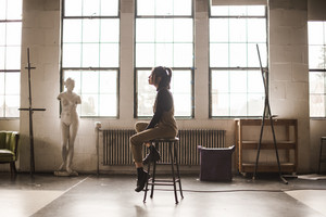 side view of asian woman sitting on a stool in an artist's studio