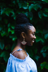 sideview image of a smiling black woman with braids high up in a ponytail wearing an off shoulder blue shirt