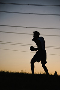 silhouette of an athlete working out outside during sunset