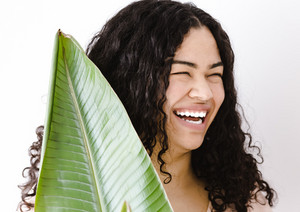 smiling woman poses with a giant leaf