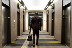tall man in a suit walks towards hotel elevators with a duffle bag