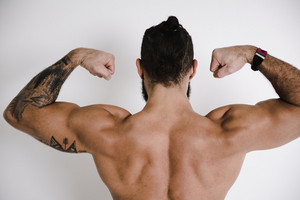 tatted athletic man flexes his back muscles