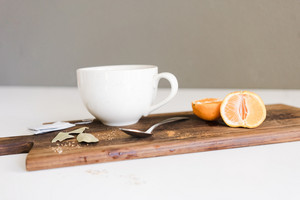 tea cup with a spoon and orange slices on wooden table