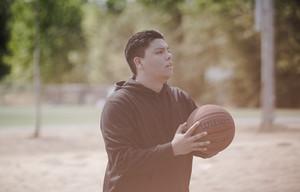 Teenage boy gripping basketball