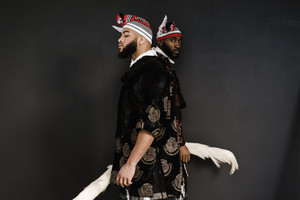 two african men in Nigerian garb standing back to back holding flywhisks