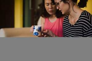 two asian women drink coffee tea and on the phone