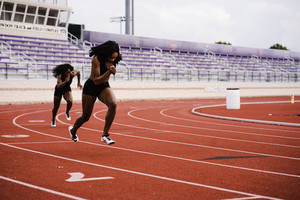 two Black female athletes running on a track