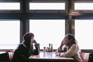 Two friends sit in a diner