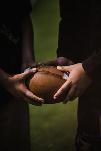 Two hands touching a football