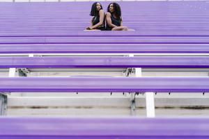 two women doing a workout on the stadium bleachers