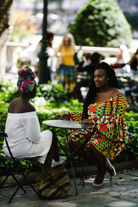 Two women sitting outside at a African gathering