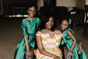 Two young Ghanaian girls in a silk green dress stand next to their mom