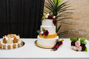 wedding cake and gingerbread cake on table with flowers