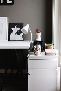 white desk and stand with drawers with office supplies skull and plant