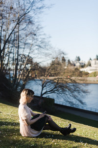 white woman sitting on grass hill in front of trees and water