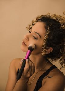 woman applies makeup with brush