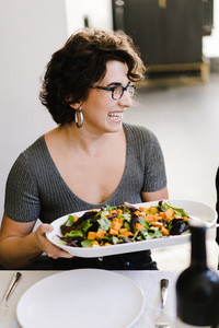 woman brings out a large dish full of food to the dining table
