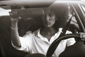 woman checking mirror in her car in a black and white photo