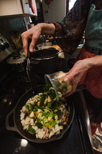 woman cooking vegetables in pan on the stove wearing festive chef apron