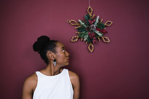 woman looks at holiday decor on the wall above her