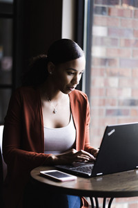 woman on a laptop with her cell phone on a table