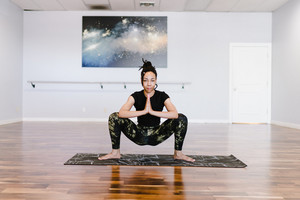 woman performs yoga poses on a wooden floor