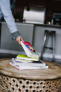 woman picking up book from pile on table