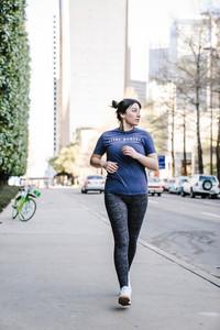 woman power walks on sidewalk in the city