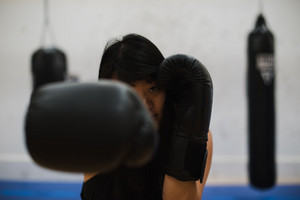 woman punches boxing gloves in the air