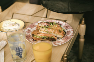 woman puts down plate with breakfast
