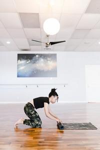 woman rolls out yoga mat on studio floor