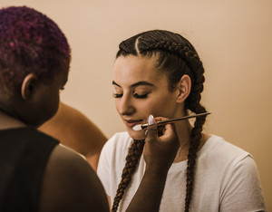 woman sitting down as makeup is applied on her